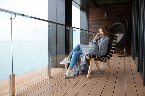 Smiling young woman sitting wrapped in knitted coverlet on the glass balcony