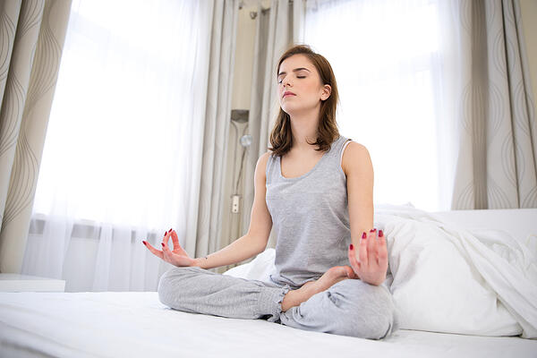 Beautiful woman doing yoga exercises on the bed at home