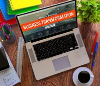 Business Transformation Concept. Modern Laptop and Different Office Supply on Wooden Desktop background.