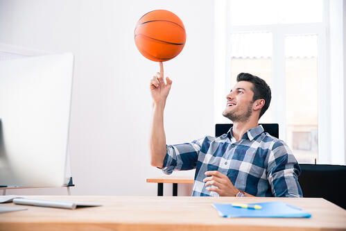 Happy businessman in casual cloth sitting at the table and spinning ball in office