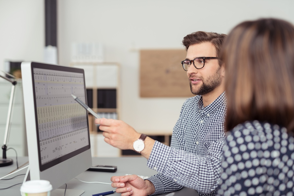 Proficient young male employee with eyeglasses and checkered shirt, explaining a business analysis displayed on the monitor of a desktop PC to his female colleague, in the interior of a modern office