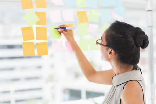Smiling designer writing on sticky notes on window in creative office