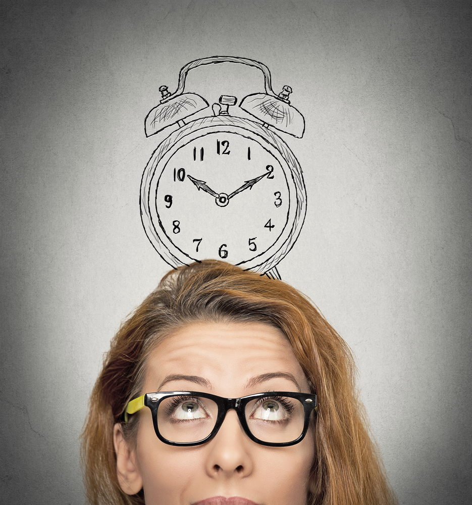 closeup headshot young business woman with alarm clock drawing sketch above her head, isolated grey wall background. Human face expressions, emotions. Time, punctuality, busy schedule concept